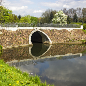 Stone bridge over the river in spring in the park
